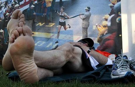Eric Maki, of Cortland N.Y., rested in front of a picture of Bill Rodgers on the Hopkinton Common before the race.